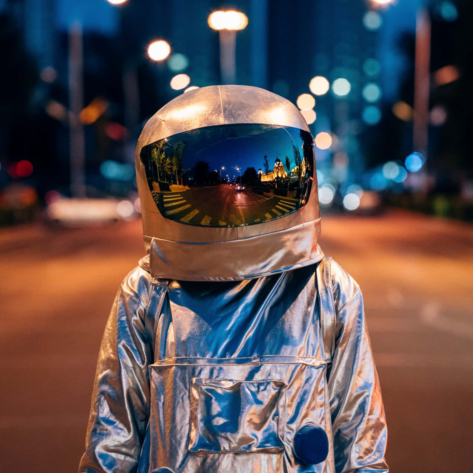 Spaceman on a street in a city at night